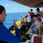 Megan briefs on how to signal air pressure under water.