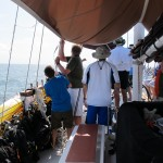 Hoisting the staysail, as seen from under the awning over the foremain.