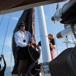 Raising the sails, Denny and Megan climb on the pilot house roof to coax the lines along the mast.